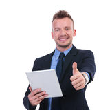 Business man holds tablet and shows thumb up. Young business man holding a tablet and showing thumb up while smiling to the camera. on white background Stock Image