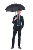 Business man holds umbrella and hand in pocket Stock Images