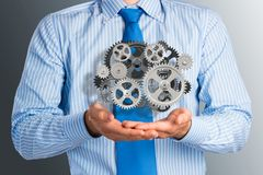 Business man holds up a mechanism of gears Stock Images