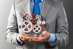 Business man holds up a mechanism of gears Royalty Free Stock Image