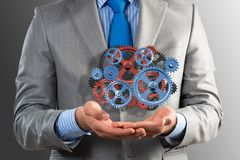 Business man holds up a mechanism of gears Stock Photography