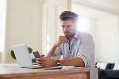 Business man at home office with smart phone and laptop. Indoor shot of young man reading text message on mobile phone while sitting at table at home. Business royalty free stock photo