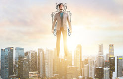 Business man hover over city skyline. Business Advantage. Businessman in sketch astronaut costume hovering over down town on sunset Royalty Free Stock Images