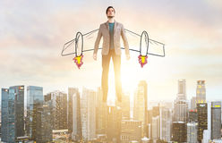 Business man hover over city skyline. Business Advantage. Businessman with sketch wings hovering over down town on sunset Stock Photography