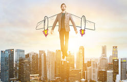 Business man hover over city skyline. Business Advantage. Businessman with sketch wings hovering over down town on sunset Stock Image