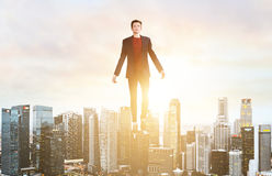 Business man hover over city skyline. Businessman hovering over down town on sunset Royalty Free Stock Photography