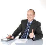 Business man II. Isolated, smiling business man sitting behind a desk; showing his thumb for o.k royalty free stock images