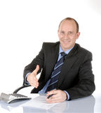 Business man III. Isolated, smiling business man sitting behind a desk, offer to shake hands stock images