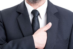 Business man inserting hand inside suit jacket Stock Photography
