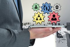 Business man interacting with people in cogs graphics against office background. Digital composite of Business man interacting with people in cogs graphics Royalty Free Stock Image
