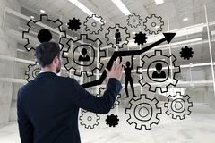 Business man interacting with people in cogs graphics against office background. Digital composite of Business man interacting with people in cogs graphics Royalty Free Stock Photography
