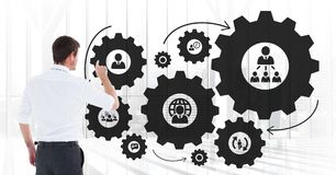 Business man interacting with people in cogs graphics against office background. Digital composite of Business man interacting with people in cogs graphics Royalty Free Stock Photo