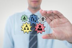 Business man interacting with people in cogs graphics against white background Royalty Free Stock Images