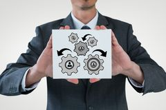 Business man interacting with people in cogs graphics against white background. Digital composite of Business man interacting with people in cogs graphics Royalty Free Stock Image