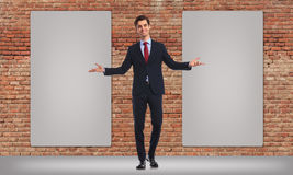 Business man inviting you to see his big billboards. Happy business man inviting you to see his twon blank big billboards Royalty Free Stock Photo