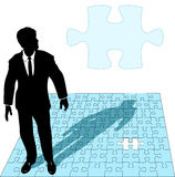 Business Man Jigsaw Puzzle Solution. A business man in a suit works the last missing piece of a jigsaw puzzle solution, as copyspace vector illustration