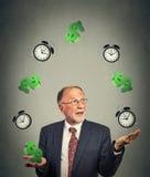 Business man juggling multiple alarm clocks and dollar sings Stock Photos