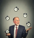 Business man juggling multiple alarm clocks. Portrait senior business man in suit juggling multiple alarm clocks isolated on gray office wall background. Timing stock photo
