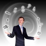 Business man juggling with numbers and symbols. Businessman in blue suit standing and juggling business symbols Stock Images
