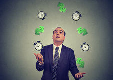 Business man juggling throwing up alarm clocks dollar signs. Time is money concept Royalty Free Stock Photos