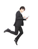 Business man jump touching tablet pc. Cheerful, full length, isolated on white background, asian man Stock Photography