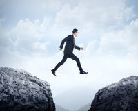 Business man jumping across hill Royalty Free Stock Photo