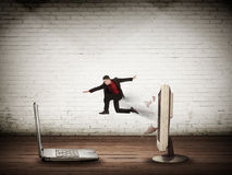 Business man jumping from desktop computer to laptop Royalty Free Stock Photography