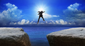 Business man jumping to next cliff with risk decision Royalty Free Stock Photos