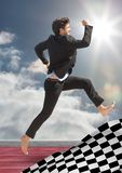 Business man jumping on track behind checkered flag and against sky with sun. Digital composite of Business man jumping on track behind checkered flag and Stock Image