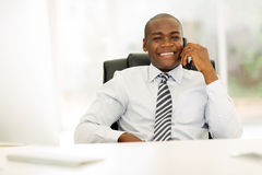 Business man landline phone. African business man talking on landline phone in modern office Stock Photography