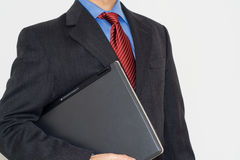 Business man with a laptop. On is arm Royalty Free Stock Photography