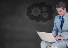 Business man with laptop against grey wall and cloud with gear graphic Stock Photography