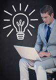 Business man with laptop against white lightbulb graphic and navy background. Digital composite of Business man with laptop against white lightbulb graphic and Stock Photo
