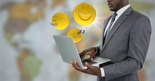 Business man with laptop and emojis with flare against blurry map. Digital composite of Business man with laptop and emojis with flare against blurry map Stock Photo