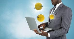 Business man with laptop and emojis with flares against blue background with cloud. Digital composite of Business man with laptop and emojis with flares against Stock Photo
