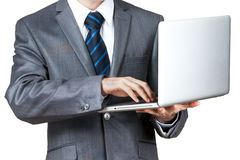 Business man with a laptop - isolated over a white background. Business man with a laptop and blue tie - isolated over a white background Stock Photos