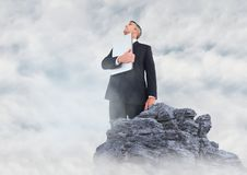 Business man with laptop looking up on rock in clouds. Digital composite of Business man with laptop looking up on rock in clouds Stock Image
