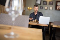 Business Man With Laptop And Mobilephone Having. Young business man with laptop and mobilephone having meal in restaurant Stock Image