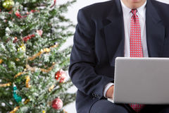 Business man with laptop near christmas tree Stock Photography