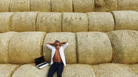 Business man with a laptop resting on straw bales. Flying drone. Ecology. Natural product. Series. stock footage
