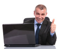 Business man at laptop, shows thumb up sign Stock Photo