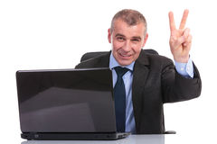 Business man at laptop, shows victory sign Royalty Free Stock Photography