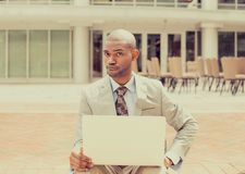 Business man with laptop skeptically looking at you camera Stock Photos