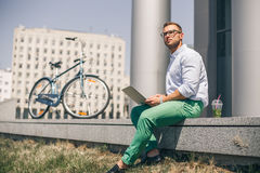 Business man with laptop and sport bike sitting in city. University student with pc and bicycle outdoor. Freelance young guy work with computer outside Stock Photos