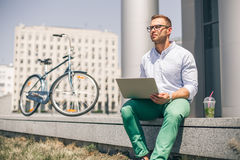 Business man with laptop and sport bike sitting in city. University student with pc and bicycle outdoor. Freelance young guy work with computer outside Royalty Free Stock Photography