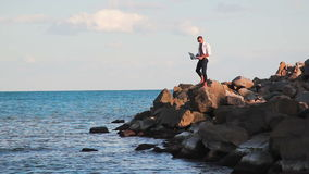 Business man on large rocks by the sea with the joy of victory with a laptop raises his hand up. The joy of victory stock video footage