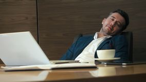 Business man leaning back on chair and relaxing with closed eyes in office. Tired man sleeping on chair at table in business office stock footage