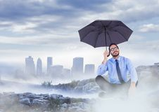 Business man legs crossed with umbrella on misty mountain peak against skyline Stock Photos