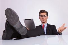 Business man legs on desk holding tablet stock image