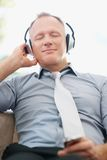 Business man listening to music on an mp3 player Stock Image